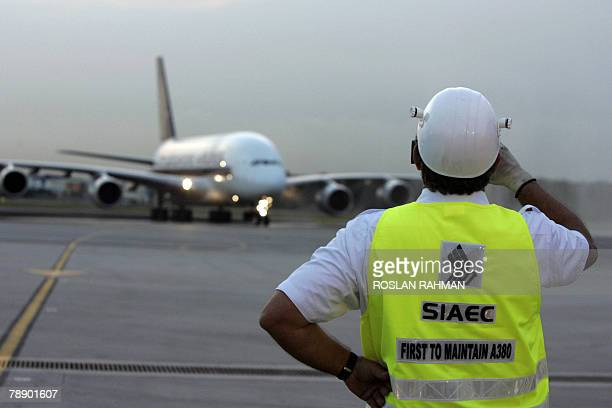 In this photo taken 17 October 2007 shows a Singapore Airlines engineering crew watches as the Airbus A380 arrives in Singapore Changi International...