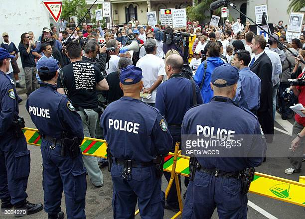 In this photo taken 24 February 2004 police watch members of the Aboriginal community from the inner Sydney suburb of Redfern as they protest outside...