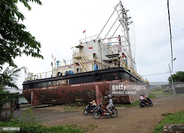 In this photo taken December 2 2009 motorcycle riding residents pass a power barge permanently marooned inland in Banda Aceh nearly five years ago...