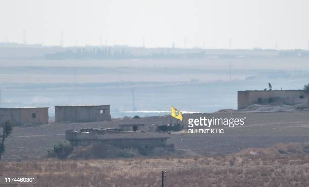 In this photo taken from the Turkish side of the border between Turkey and Syria in Akcakale Sanliurfa province southeastern Turkey a flag of Kurdish...