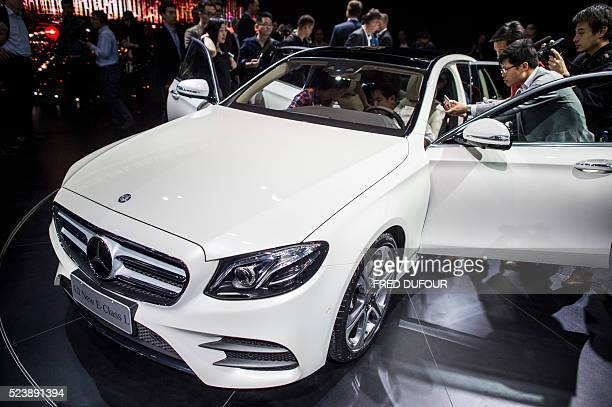 In this photo taken in Beijing on April 24 Chinese journalists gather to look at the new Mercedes Benz EClass Long Wheelbase during the 'Auto China...