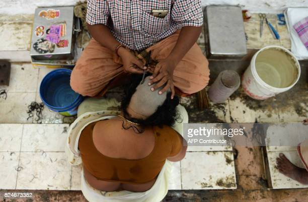 In this photo taken July 19 Indian Hindu devotee Vanaja gets her head shaved at the Thiruthani Murugan Temple in Thiruthani in India's southern state...