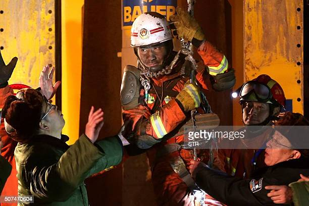 TOPSHOT In this photo taken late January 29 rescuers free a trapped miner in Pingyi County eastern China's Shandong province The first three of four...