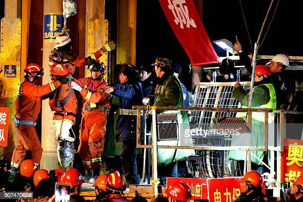 In this photo taken late January 29 rescuers free a trapped miner in Pingyi County eastern China's Shandong province The first three of four...
