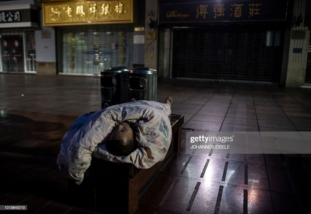 In this photo taken late on August 8, 2018, a man sleeps on a bench along Nanjing East Road, a popular pedestrian street filled with shoppers and tourists during the day, to escape the heat of residential apartments in Shanghai. - Normally bustling Nanjing East Road has turned into an open-air slumber party on recent nights as local residents try to beat the heat of their cramped nearby homes by sleeping outside on benches or directly on the pavement. Many homes in some of Shanghai's low-rise older neighbourhoods lack air conditioning, while residents that do have it will often seek ways to keep electricity bills from skyrocketing during summer.