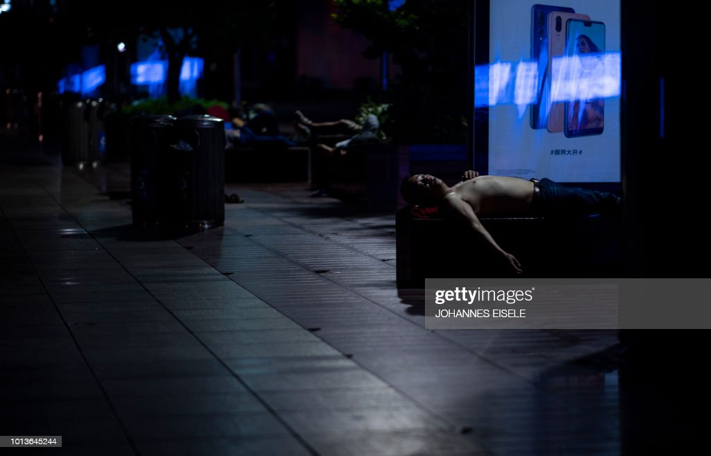 In this photo taken late on August 8, 2018, men sleep on benches along Nanjing East Road, a popular pedestrian street filled with shoppers and tourists during the day, to escape the heat of residential apartments in Shanghai. - Normally bustling Nanjing East Road has turned into an open-air slumber party on recent nights as local residents try to beat the heat of their cramped nearby homes by sleeping outside on benches or directly on the pavement. Many homes in some of Shanghai's low-rise older neighbourhoods lack air conditioning, while residents that do have it will often seek ways to keep electricity bills from skyrocketing during summer.