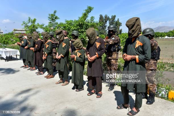 In this photo taken on April 10 members of the Afghan security forces stand behind alleged Islamic State fighters being presented to the media in...
