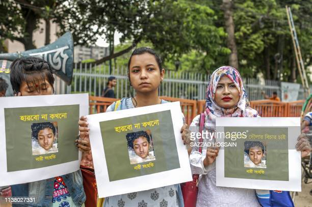 In this photo taken on April 12 2019 Bangladeshi women hold placards and photographs of schoolgirl Nusrat Jahan Rafi at a protest in Dhaka following...