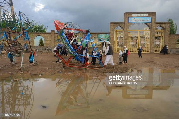 TOPSHOT In this photo taken on April 15 Afghan schoolgirls play on a swing ship in Herat province