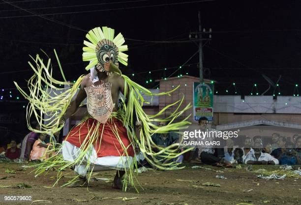 In this photo taken on April 22 an Indian performer dressed with a bird mask takes part in a Pakshi Kolam dance during the Kadammanitta Padayani...