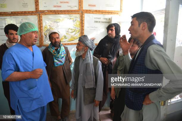 In this photo taken on August 12 2018 Afghan residents talk with a hopital staff member as they search for their relatives at a hospital in Ghazni...