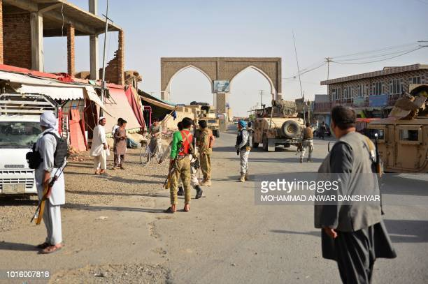 In this photo taken on August 12 2018 Afghan security forces and Afghan militia stand along a road during clashes between Taliban militants and...
