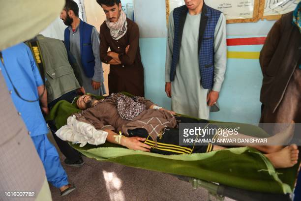 In this photo taken on August 12 2018 Afghan volunteers carry an injured man on a stretcher to a hospital in Ghazni province Afghanistan is sending...