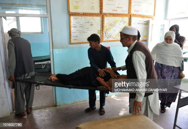 In this photo taken on August 12 2018 Afghan volunteers carry an injured woman on a stretcher to a hospital in Ghazni province Afghanistan is sending...
