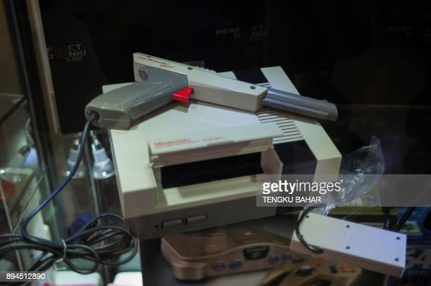 In this photo taken on August 12 a rare early production Zapper gun is seen on display with the classic 1980s era Nintendo Entertainment System 8bit...
