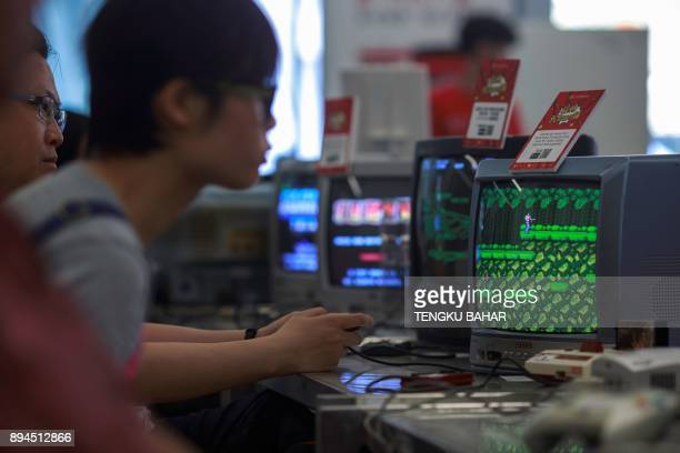 In this photo taken on August 12 a visitor plays the 1980s classic Konami game Contra on a Nintendo Famicon 8bit video console system during the...