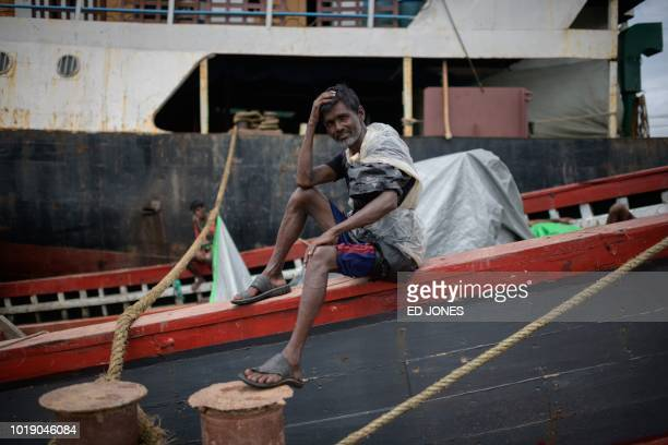 In this photo taken on August 13 a Rohingya worker sits on a boat in front of another vessel from Myanmar's Rakhine state carrying sacks of ginger at...