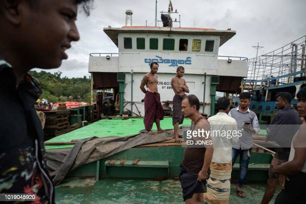 In this photo taken on August 13 crew members of a boat which arrived from Myanmar's Rakhine state watch the vessel being loaded with products from...