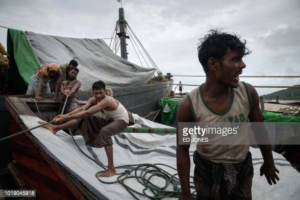In this photo taken on August 13 Rohingya and Bangladeshi workers secure a barge to a boat carrying ginger which arrived from Myanmar's Rakhine state...