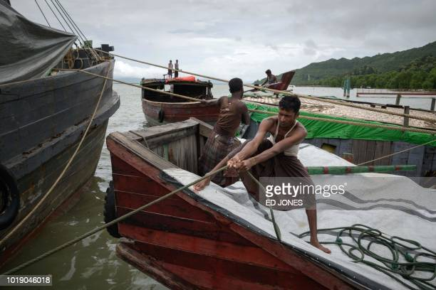 In this photo taken on August 13 Rohingya and Bangladeshi workers secure barges to a boat from Myanmar's Rakhine state at Teknaf port near Cox's...