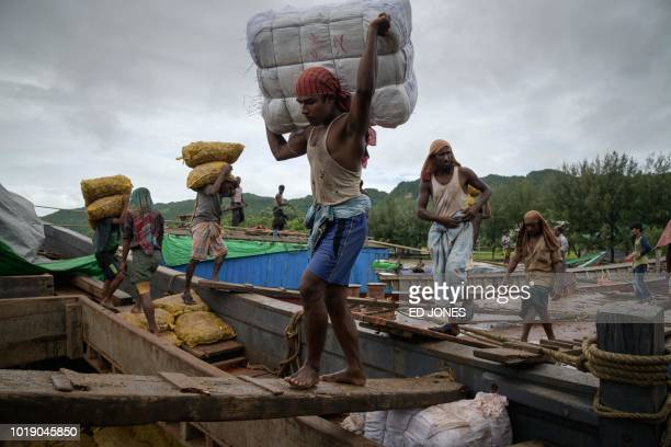 In this photo taken on August 13 Rohingya workers transfer 30kg sacks of ginger as others load products from Bangladesh onto boats travelling to and...
