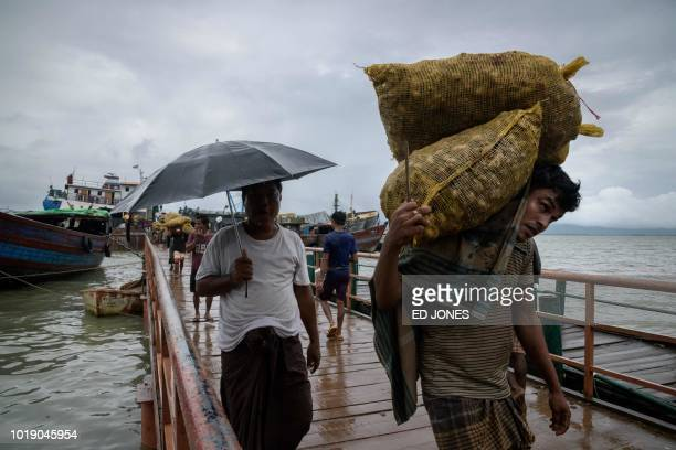 In this photo taken on August 13 Rohingya workers transfer 30kg sacks of ginger from a boat which arrived from Myanmar's Rakhine state to waiting...