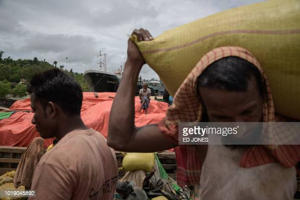 In this photo taken on August 13 Rohingya workers transfer sacks of dried fish from a barge at Teknaf port near Cox's Bazar The Bangladeshi district...