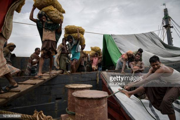 In this photo taken on August 13 Rohingya workers transport 30kg sacks of ginger from a boat which arrived from Myanmar's Rakhine state at Teknaf...