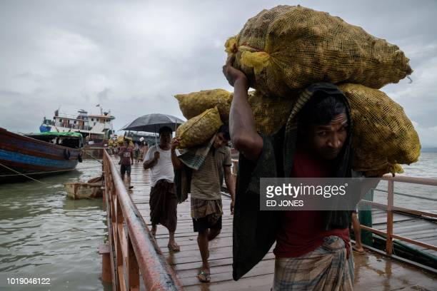 In this photo taken on August 13 Rohingya workers transport 30kg sacks of ginger from a boat which arrived from Myanmar's Rakhine state to waiting...