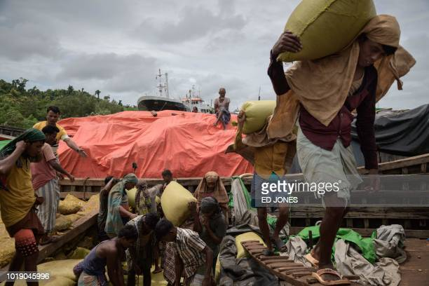 In this photo taken on August 13 Rohingya workers transport sacks of dried fish from a barge at Teknaf port near Cox's Bazar The Bangladeshi district...