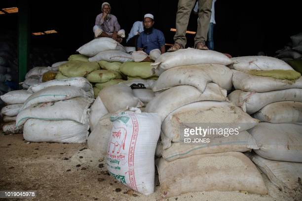 In this photo taken on August 13 workers stand atop a pile of rice sacks from Myanmar in a warehouse at Teknaf port near Cox's Bazar The Bangladeshi...