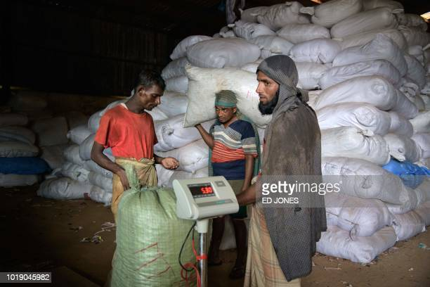 In this photo taken on August 13 workers weigh sacks of rice from Myanmar before carrying them to waiting trucks at Teknaf port near Cox's Bazar The...