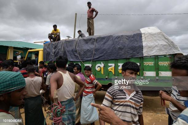 In this photo taken on August 14 Rohingya refugees collect boxes of food aid at a distribution point in the Kutupalong camp near Cox's Bazar The...