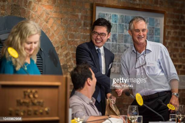 In this photo taken on August 14 Victor Mallet a Financial Times journalist and vice president of the Foreign Correspondents' Club shakes hands with...