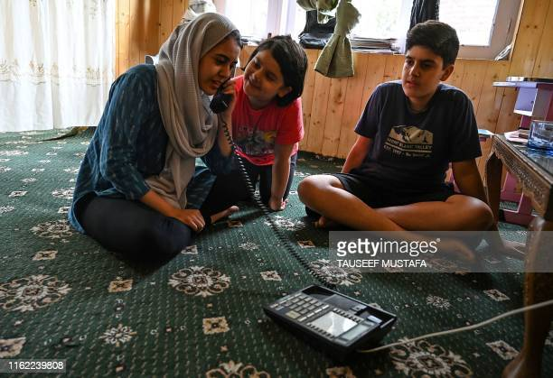 In this photo taken on August 17 a Kashmiri Muslim family talks to relatives on a landline phone in Srinagar Seventeen out of around 100 telephone...