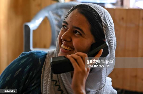 In this photo taken on August 17 a Kashmiri Muslim looks on as she talks to relatives on a landline phone in Srinagar Seventeen out of around 100...
