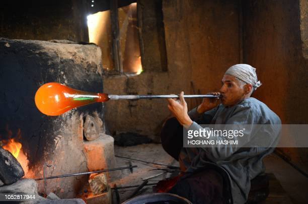 In this photo taken on August 2 Afghan man glassblower Ghulam Sakhi mid40s crafts a glass object at his traditional glassblowing workshop in Herat...