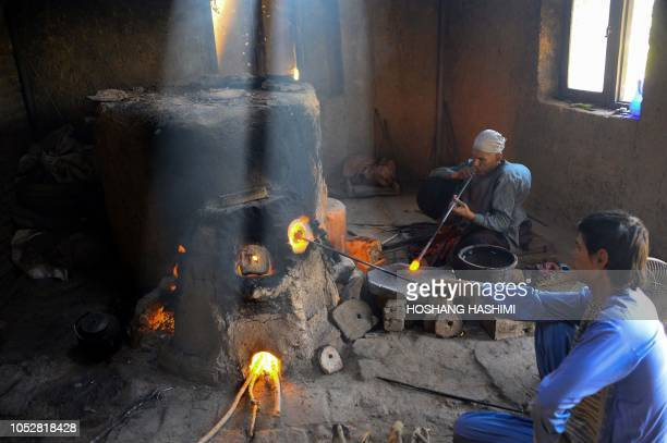 In this photo taken on August 2 Afghan man glassblower Ghulam Sakhi mid40s with his son Habibullah crafts a glass object at his traditional...