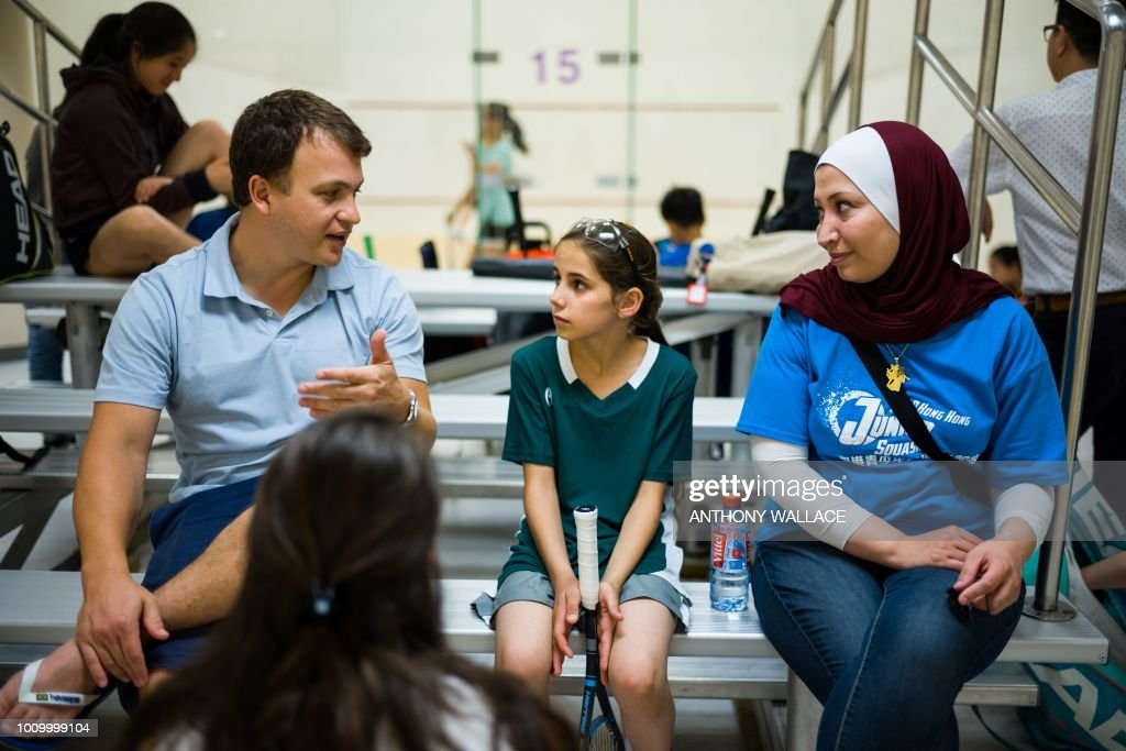 In this photo taken on August 2, 2018, Clayton Kier (L), executive director of Squash Dreamers, a US NGO based in Jordan, and team coach Reem Niaz (R), a refugee from Damascus, speak with Syrian squash player Sabah Husryeh (C), 11, during the Hong Kong Junior Squash Tournament at the Cornwall Street Park Squash Centre in Hong Kong. - Three young Syrian squash players, aged between 11 and 13, are part of a new team called Squash Dreamers, made up of displaced Syrian youngsters who were forced to flee their war-torn homeland. (Photo by Anthony WALLACE / AFP) / TO GO WITH HongKong-Syria-sport-squash-refugee by Yan ZHAO