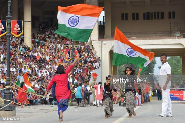 In this photo taken on August 2 Indian girls wave national flags during the nightly ceremony at the IndiaPakistan border in Wagah From barbed grins...