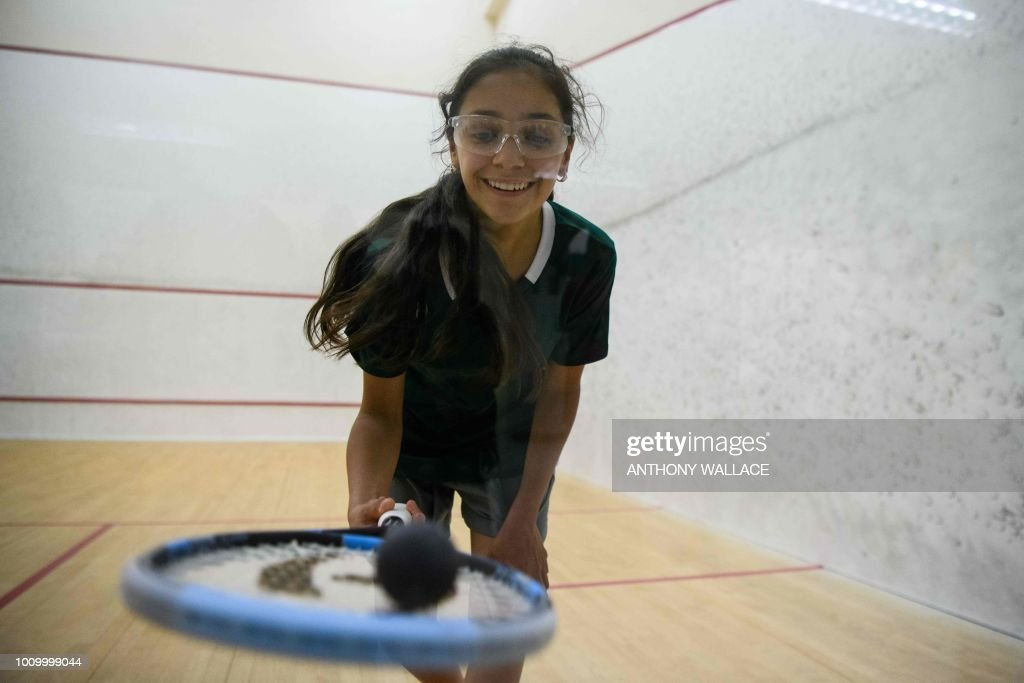 In this photo taken on August 2, 2018, Syrian squash player Raghda Husryeh, 13, of Squash Dreamers, a US NGO based in Jordan, lifts the ball from the court during the Hong Kong Junior Squash Tournament at the Cornwall Street Park Squash Centre in Hong Kong. - Three young Syrian squash players, aged between 11 and 13, are part of a new team called Squash Dreamers, made up of displaced Syrian youngsters who were forced to flee their war-torn homeland. (Photo by Anthony WALLACE / AFP) / TO GO WITH HongKong-Syria-sport-squash-refugee by Yan ZHAO