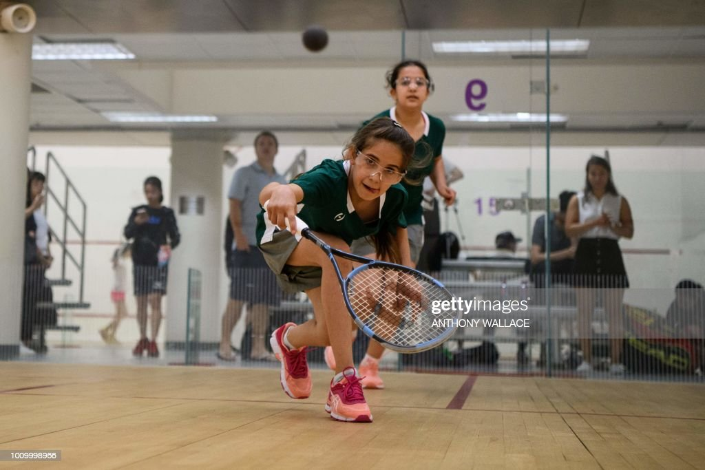 In this photo taken on August 2, 2018, Syrian teammates of Squash Dreamers, a US NGO based in Jordan, Sabah Husryeh, 11 (front), and Eman Hassan (behind), 12, play on a court during the Hong Kong Junior Squash Tournament at the Cornwall Street Park Squash Centre in Hong Kong. - Three young Syrian squash players, aged between 11 and 13, are part of a new team called Squash Dreamers, made up of displaced Syrian youngsters who were forced to flee their war-torn homeland. (Photo by Anthony WALLACE / AFP) / TO GO WITH HongKong-Syria-sport-squash-refugee by Yan ZHAO