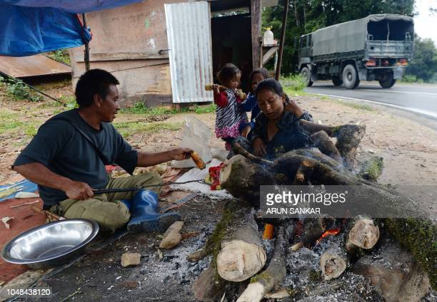 In this photo taken on August 24 a Bhutanese man roasts corn over a wood fire with his family on the roadside near Dochula Pass The gentle whirring...