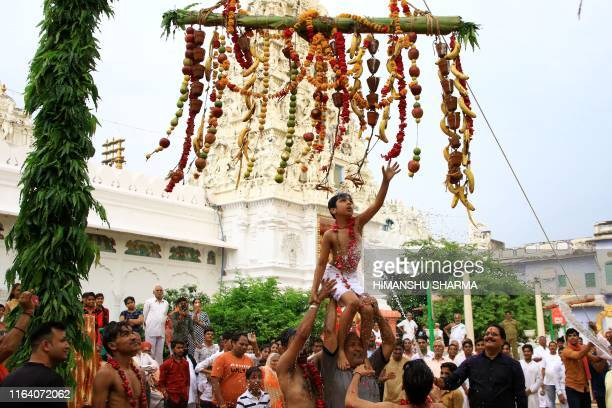 TOPSHOT In this photo taken on August 25 2019 a Hindu youth is sprayed with water as he takes part in a ritual to mark the Janmashtami festival which...