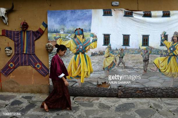In this photo taken on August 25 a Bhutanese women walks past a mural representing folk performance at the Simply Bhutan museum in Thimphu.