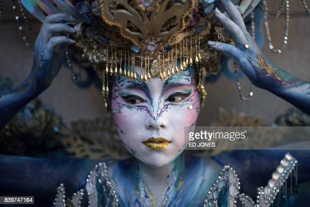 TOPSHOT In this photo taken on August 26 a contestant of the 'fantasy' category prepares to be judged during the Daegu International Bodypainting...