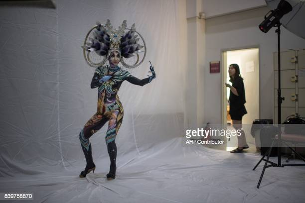 In this photo taken on August 26 a model poses for a photo backstage before presenting herself to the audience during the Daegu International...