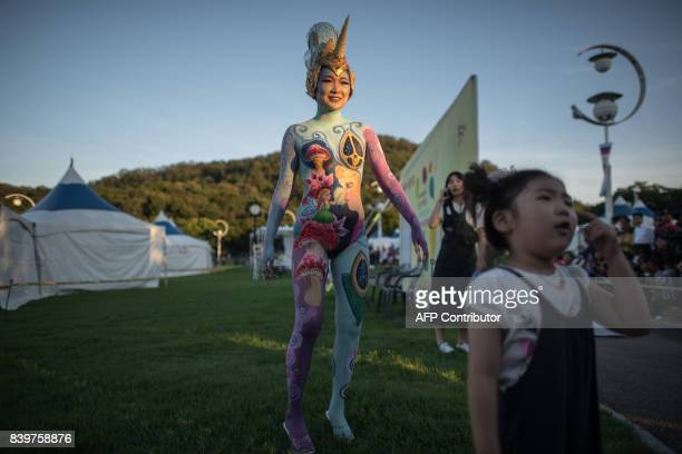 In this photo taken on August 26 a model poses for photos during the Daegu International Bodypainting Festival in Daegu The bodies of dozens of...