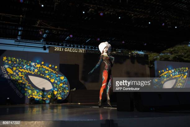 In this photo taken on August 26 a model poses on stage during during the Daegu International Bodypainting Festival in Daegu The bodies of dozens of...
