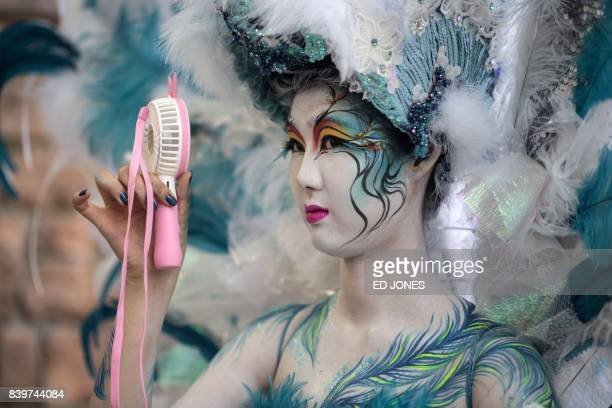 TOPSHOT In this photo taken on August 26 a model uses a portable fan to keep cool backstage during the Daegu International Bodypainting Festival in...